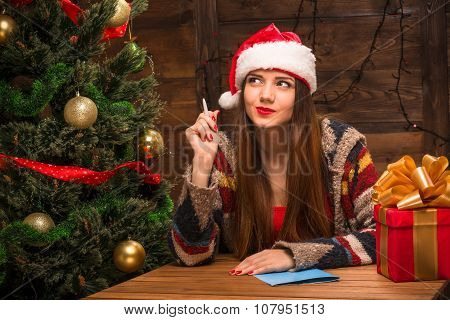 Beautiful girl writing New Year and Christmas congratulation