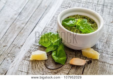 Pesto sauce in bowl, rustic wood background