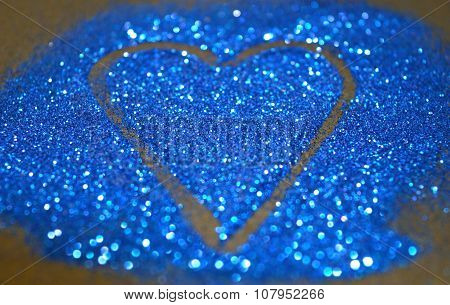 Blurry abstract background with heart of blue glitter sparkle on black surface