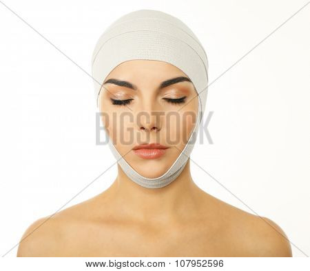 Young beautiful woman with closed eyes and an elastic bandage on her head, isolated on white