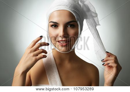 Young emotional woman with a gauze bandage on her head, on grey background