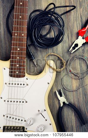 Electric guitar with musical equipment on wooden background