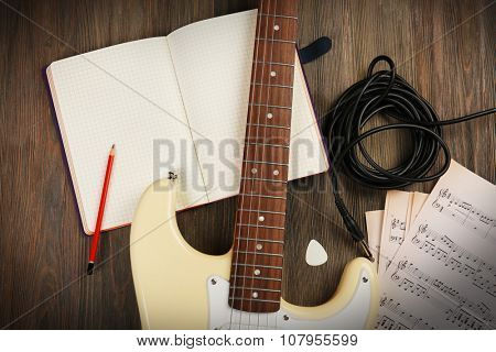 Electric guitar with musical notes and cord on wooden background
