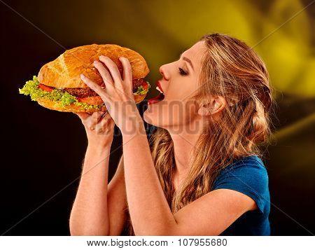 Young woman  biting big hamburger. Fastfood concept.