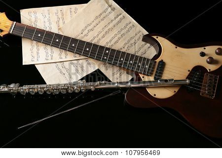 Flute, electric guitar and note sheets on black background