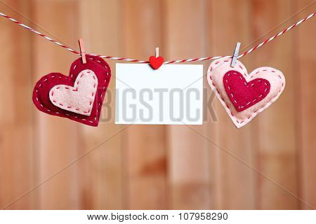 Textile hearts and empty sheet hanging on cord against wooden background