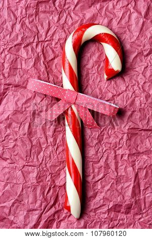Closeup of an old fashioned candy cane with a polka dot bow. Vertical format on crumpled red tissue paper.