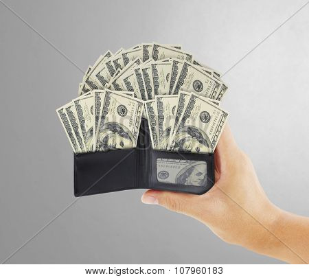 dollar in  black leather wallet in hand