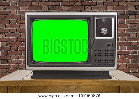 Old television with chroma key green screen and brick wall.