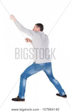 back view of standing man pulling a rope from the top or cling to something. guy watching. Rear view people collection.  backside view of person.  Isolated over white background. legs apart man pulls