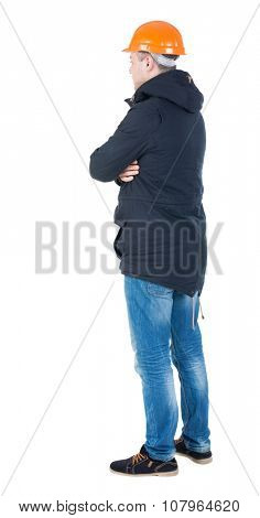 Backview of an engineer in construction helmet stands and parka. Standing young guy. Rear view people collection.  backside view of person.  Isolated over white background.
