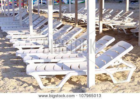 Plastic sunbeds on sandy beach, close up