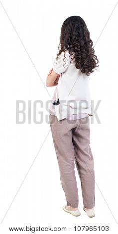 back view of standing young beautiful  woman.  girl  watching. Rear view people collection.  backside view of person. Isolated over white background. curly girl standing sideways with his arms crossed