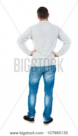 Back view of man in jeans. Standing young guy. Rear view people collection.  backside view of person.  Isolated over white background. A guy in a gray jacket is placing hands on the belt.
