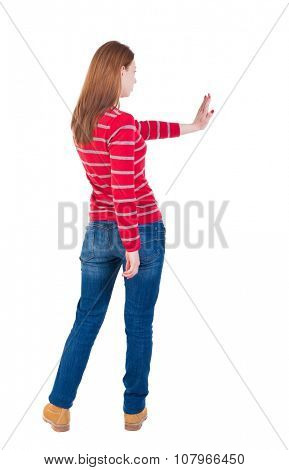 back view of woman. Young woman presses down on something. Isolated over white background. Rear view people collection. backside view of person. she holds his hand open, palm forward.