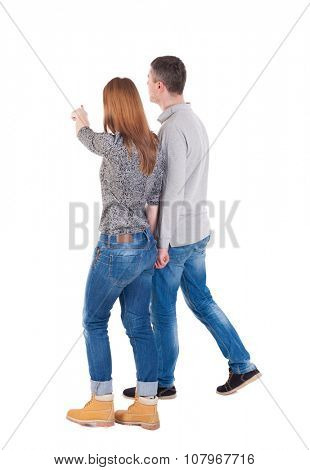 Back view of walking young couple (man and woman) pointing. Rear view people collection. backside view of person. Isolated over white