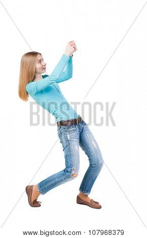 back view of standing girl pulling a rope from the top or cling to something. girl  watching. Rear view people collection.  backside view of person.  Isolated over white background.