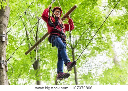 Child reaching platform climbing in high rope course