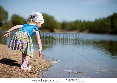 Little Girl Throwing Stones Into A Lake