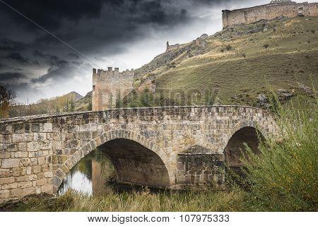 ancient Roman bridge over Ucero river and a castle - El Burgo de Osma town, Soria, Spain