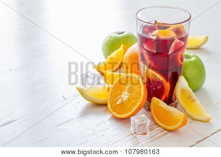 Sangria and ingredients on white wood background