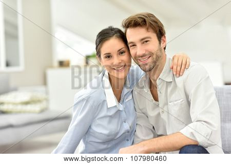 Portrait of cheerful couple sitting in sofa at home