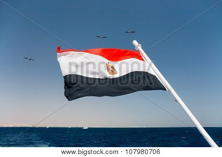 The National Flag Of Egypt Is Flapping In The Wind Above The Red Sea.