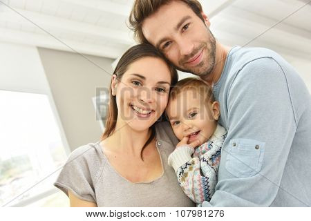 Portrait of happy parents holding baby girl
