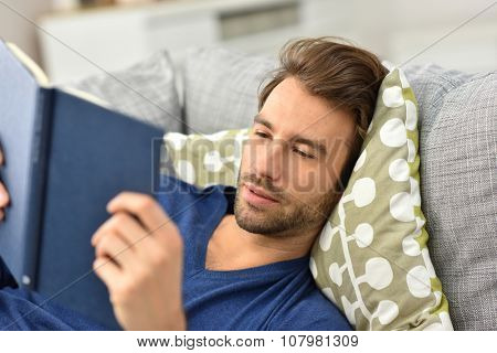 Man relaxing in sofa and reading book