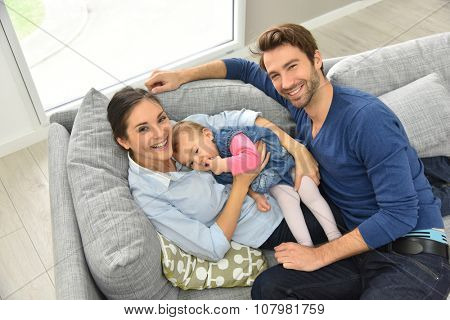Upper view of young family relaxing in sofa