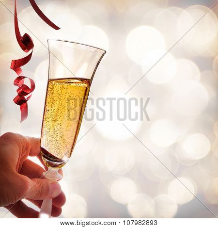 Hand Holding A Glass Of Sparkling White Wine And Ribbons
