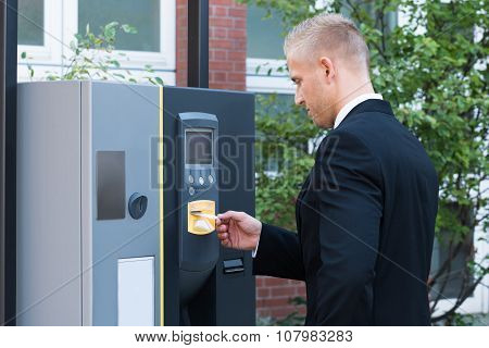 Man Inserting Ticket To Pay For Parking