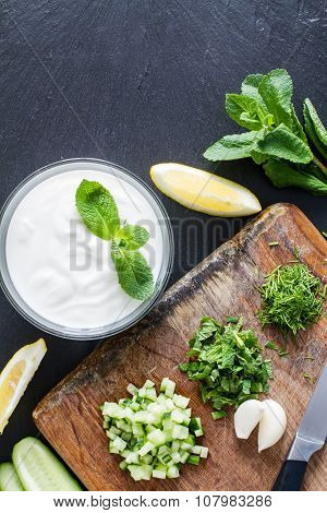 Preparing tzatziki sauce and ingredients, dark stone background
