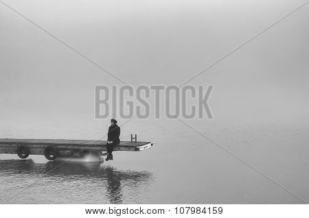 Lonely Sad Girl Sitting On Wooden Dock And Watching River Flow On Misty Autumn Day