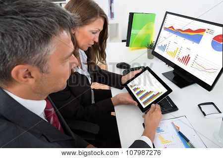 Businesspeople Analyzing Graph On Digital Tablet