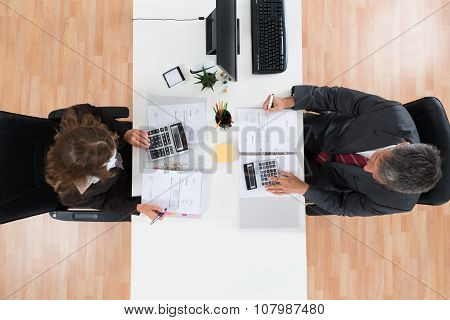Two Businesspeople Calculating Bills In Office