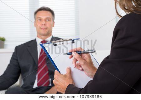 Psychiatrist Writing On Clipboard In Front Of Patient