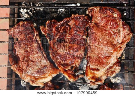 fresh hot bbq grill red beef meat steak ready on grid over charcoal with marks