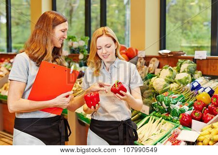 Salesclerk in training getting help from staff in a supermarket