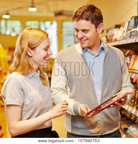 Customer seeking advice from saleswoman in a supermarket