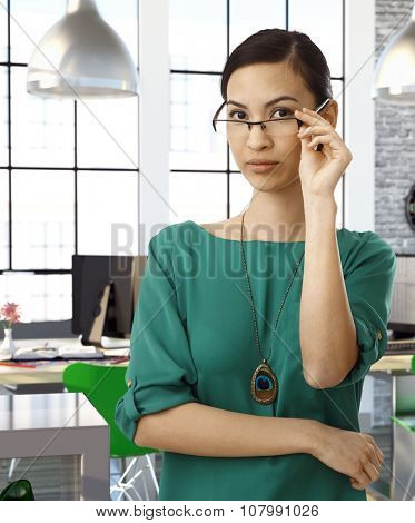 Asian female officeworker at office wearing green blouse standing and raising glasses.