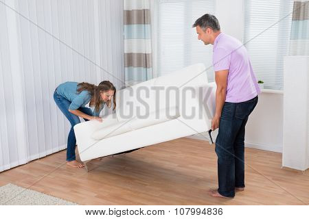 Couple Trying To Move A Couch