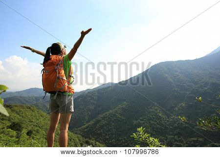 young woman hiker on mountain peak