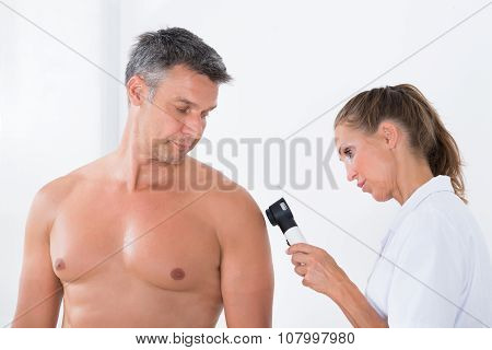 Doctor Examining Pigmented Skin Of Patient