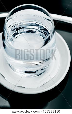 Single glass of clean clear drinking water close up macro on the table