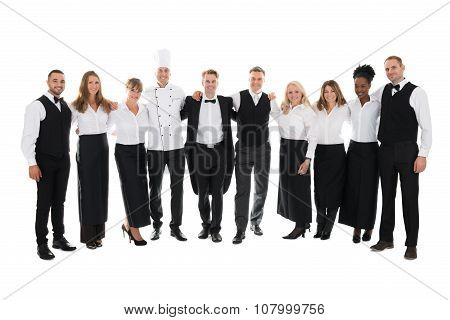 Confident Restaurant Staff Standing With Arms Around