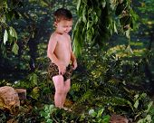 stock photo of tarzan  - A happy preschooler playing Tarzan in a jungle - JPG