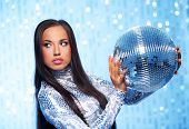 Brunette woman with a disco ball over abstract background