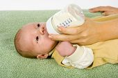 picture of babygro  - woman feeds her newborn son using bottle - JPG
