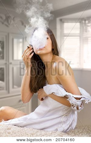 woman in prom dress smokes cigaret after farewell party